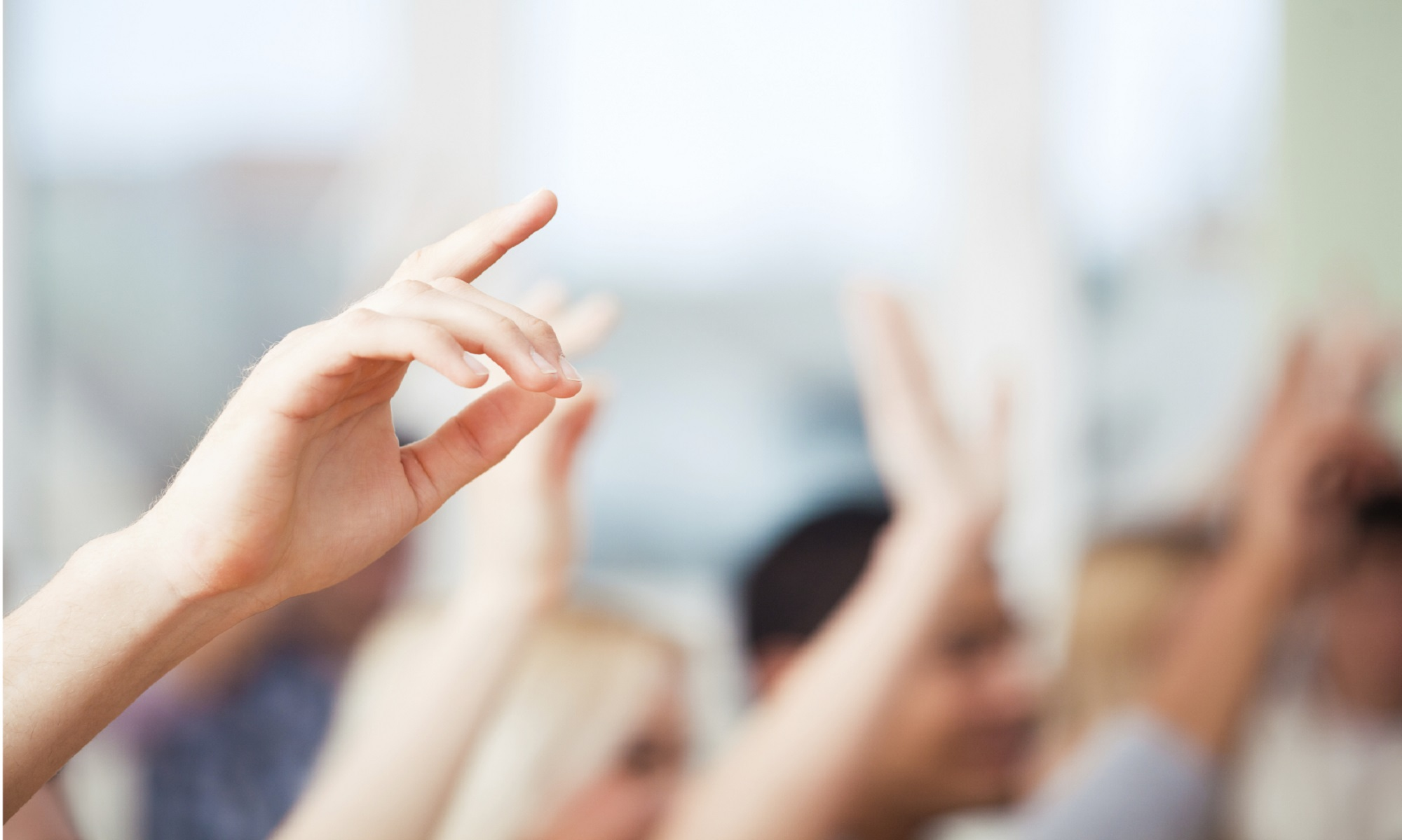 A picture of the raised hands of students